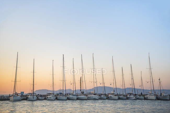 Sailing boats in a row at sunset on Agistri Island, Saronic Islands, Greek Islands, Greece — Stock Photo