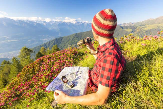 Viandante con mappa e binocolo seduto e guardando la vista Alpi Retiche, Valle del Bitto, Lombardia, Italia — Foto stock