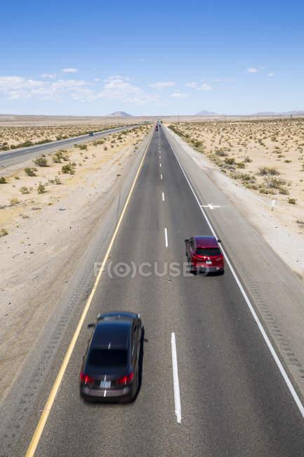 Exibição de carros dirigindo na estrada 15 no deserto da Califórnia, Estados Unidos da América, América do Norte — Fotografia de Stock