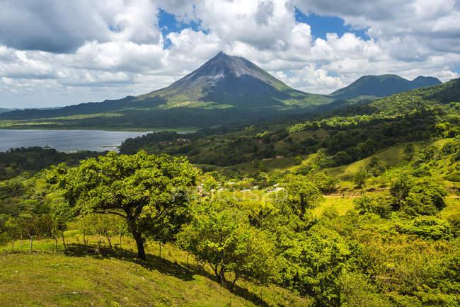 Grüne Bäume wachsen auf Hügeln und Vulkan Arenal auf Hintergrund, Provinz Alajuela, Costa Rica, Mittelamerika — Stockfoto