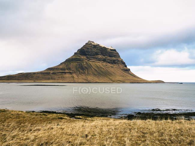 Vue du Mont Kirkjufell sous un ciel nuageux près Grundarfjordur ville du Nord de la péninsule de Snaefellsnes dans les régions polaires ouest, Islande, — Photo de stock