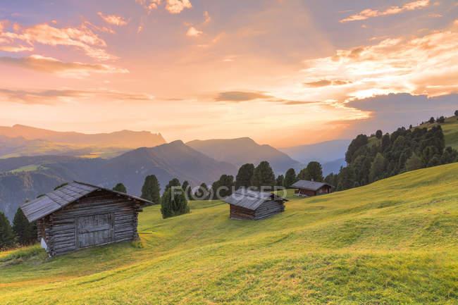 Захід сонця над традиційними хатин на пасовищі, GARDENA Valley, Південний Тироль, Доломітові Альпи, Італія, Європа — стокове фото