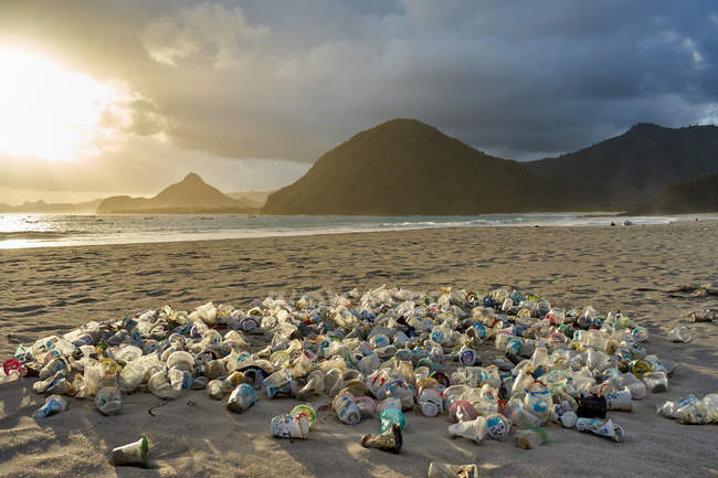Pile of plastic rubbish dumped on sand at sunset on Selong Belanak Beach on Lombok, Indonesia, Southeast Asia, Asia — Stock Photo