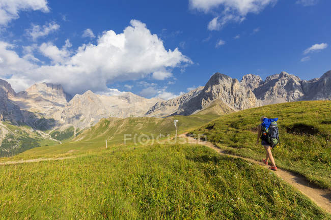 Female hiker walking on path near San Nicolo Pass, Fassa Valley, Trentino, Dolomites, Italy, Europe — Stock Photo