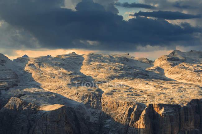 Закат над Sella плато под пасмурным небом, Piz Пордои, перевал Пордои, Фасса, Трентино, Доломиты, Италия — стоковое фото