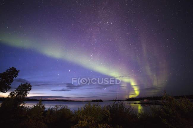 The Northern Lights (aurora borealis) in night sky above Lake Egenolf in northern Manitoba, Canada, North America — Stock Photo