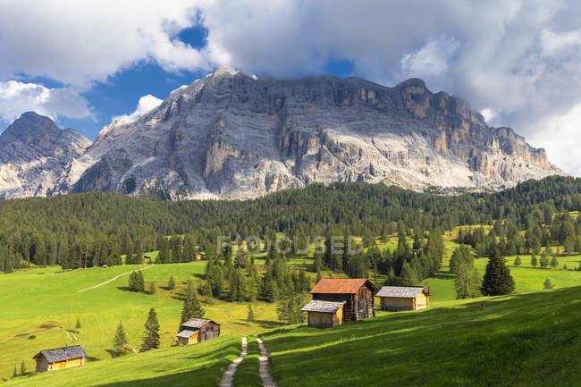 Cabanes de Prati Armentara sur la piste verte et les montagnes Rocheuses sur le fond, La Val (Wengen), vallée de Badia, Tyrol du Sud, Dolomites, Italie, Europe — Photo de stock