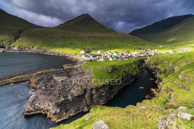 Живописные зеленые холмы и скалы с прибрежной деревне Gjogv на фоне, Эстурой острова, Фарерские острова, Дания, Европа — стоковое фото