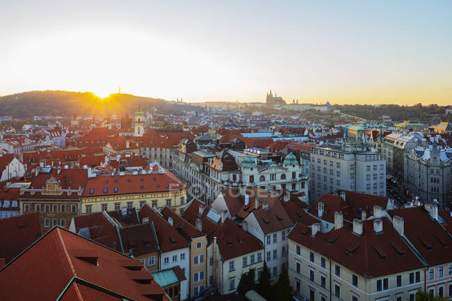 Roofs of traditional buildings and Prague Castle at sunset, Prague, Czech Republic, Europe — стокове фото