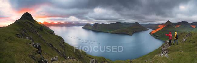 Панорамный живописный фьордов под пасмурным небом на закате с туристов на фоне, Funningur, Эстурой острова, Фарерские острова, Дания, Европа — стоковое фото