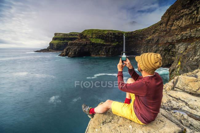 Man with smartphone taking photo at Gasadalur waterfall, Vagar island, Faroe Islands, Denmark, Europe — Stock Photo