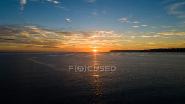 Céu do sol sobre o mar calmo watertor Bay, Paignton, Devon, Inglaterra, Reino Unido — Fotografia de Stock