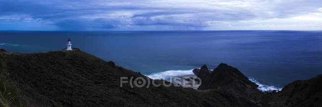Panoramic view of ocean coast at dusk with Cape Reinga Lighthouse on background, Aupouri Peninsula, Northland, North Island, New Zealand, Pacific — Stock Photo