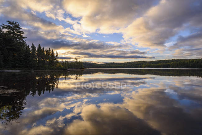 Clouds reflecting in Provoking Lake at dawn on Highland Backpacking Trail, Algonquin Provincial Park, Ontario, Canada, North America — Stockfoto