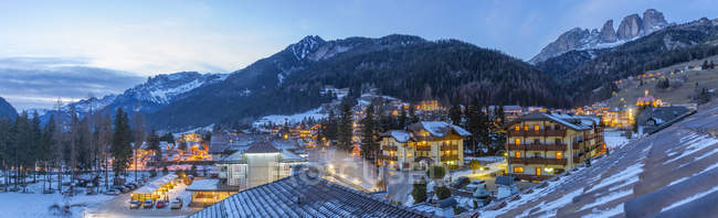 Panorama of illuminated town in winter mountains, Campitello di Fassa, Italy, Europe — Stock Photo