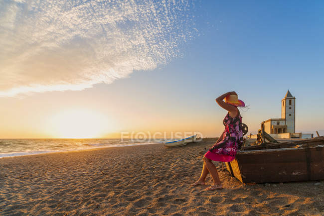 Woman sitting on boat on Iglesia de Las Salinas beach at sunset in Cabo de Gata-Nijar Natural Park, Spain, Europe — стокове фото