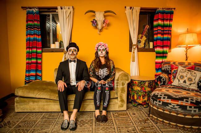 Uomo e donna in Dia de los Muertos trucco e costumi seduti sul divano, Giorno dei Morti celebrazione — Foto stock