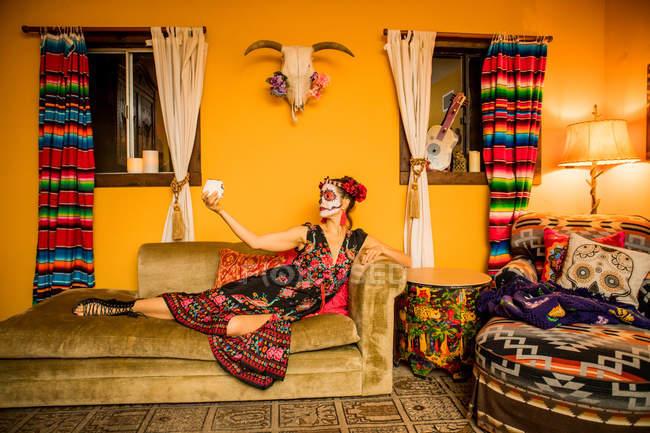 Donna in Dia de los Muertos trucco e costume sdraiato sul divano, Giorno dei Morti celebrazione — Foto stock