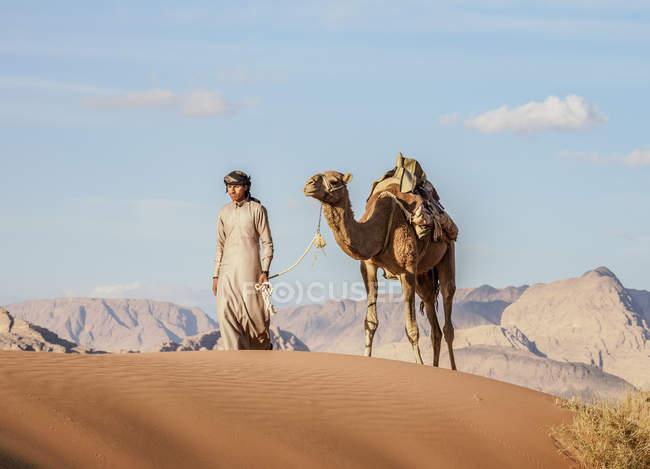 Bedouin walking with camel in desert, Wadi Rum, Aqaba Governorate, Jordan, Middle East — Fotografia de Stock