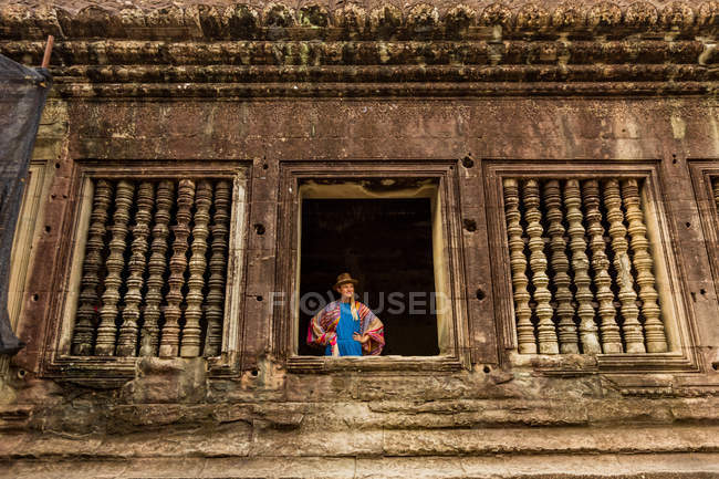 Woman tourist looking through window at Angkor Wat, Angkor, Siem Reap, Cambodia, Indochina, Southeast Asia, Asia — Stock Photo