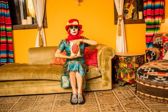 Donna in Dia de los Muertos trucco e costume seduto sul divano, Giorno dei Morti celebrazione — Foto stock