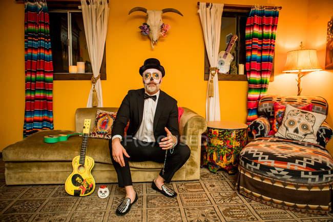 Uomo in Dia de los Muertos trucco e costume seduto sul divano, Giorno dei Morti celebrazione — Foto stock