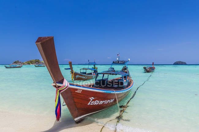 Longtail boats in turquoise water on Sunrise Beach on Ko Lipe in Tarutao National Marine Park, Thailand, Southeast Asia, Asia - foto de stock