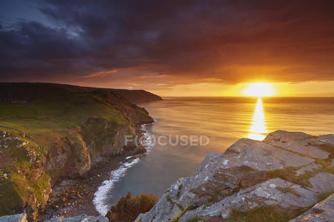 Sunset over coastal cliffs and ocean, Lynton, Exmoor National Park, Devon, England, United Kingdom, Europe — стокове фото