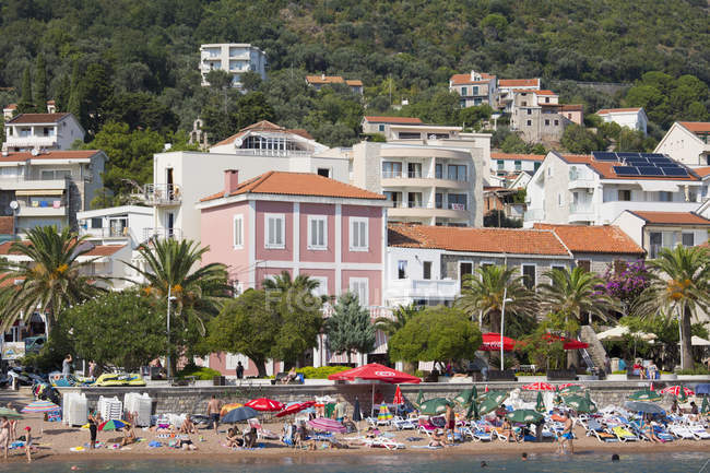 View of town beach and colorful houses overlooking the palm-lined seafront promenade, Petrovac, Budva, Montenegro, Europe — Stock Photo