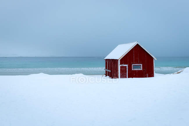 Red rorbuer fisherman hut on snowy winter day, Ramberg, Lofoten Islands, Nordland, Arctic, Norway, Europe - foto de stock