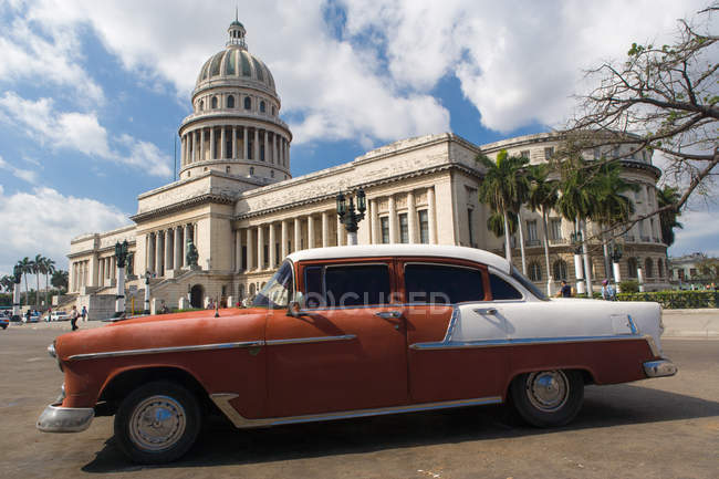 Red and white retro American car outside El Capitolio in Havana, Cuba, West Indies, Caribbean, Central America - foto de stock