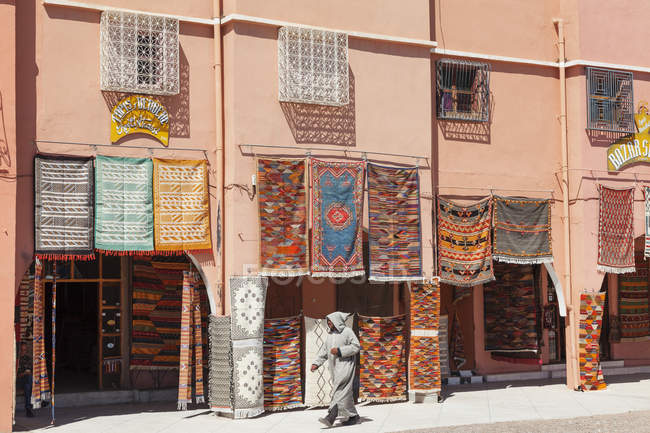 Carpets hanging outside carpet shop with local man passing by, Tazenakht, Southern Morocco, Morocco, North Africa, Africa — стокове фото