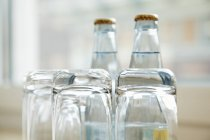 Vista de cerca de arriba abajo vasos de agua con botellas de agua en el fondo - foto de stock
