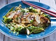 Filete de pollo con fideos de huevo, brócoli y colza en plato azul con palos de madera - foto de stock