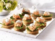 Salmon canapes with spinach and cheese — Stock Photo