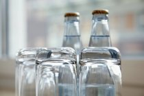 Vista de cerca de vasos y botellas de agua - foto de stock