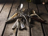 Closeup view of old silver cutlery heap on wooden planks — Stock Photo