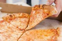 Uomo tenendo il pezzo di pizza — Foto stock