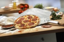 Salami pizza with pizza paddle — Stock Photo