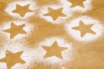 Closeup view of star shapes outlined in icing sugar on wooden background — Stock Photo
