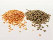 Closeup view of red and green lentils on white surface — Stock Photo