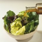 Versando il condimento sopra lattuga mista — Foto stock