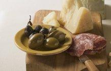 Aceitunas con salchicha en rodajas y parmesano - foto de stock
