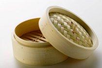 Vista del primo piano di un piroscafo di bambù aperto su superficie bianca — Foto stock