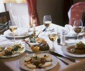 Vista de primer plano de aperitivos con vino blanco y plato de pescado en la mesa puesta - foto de stock