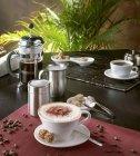 Капучино в чашку с кофе в зернах — стоковое фото