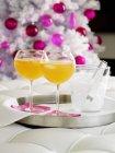 Des boissons avec des glaçons et arbre de Noël sur fond orange — Photo de stock