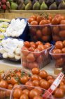 Tomatoes and mushrooms in plastic punnets — Stock Photo