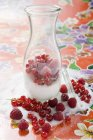 Fresh mixed berries with sugar in carafe — Stock Photo