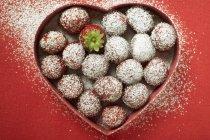 Fresas azucaradas en plato en forma de corazón - foto de stock